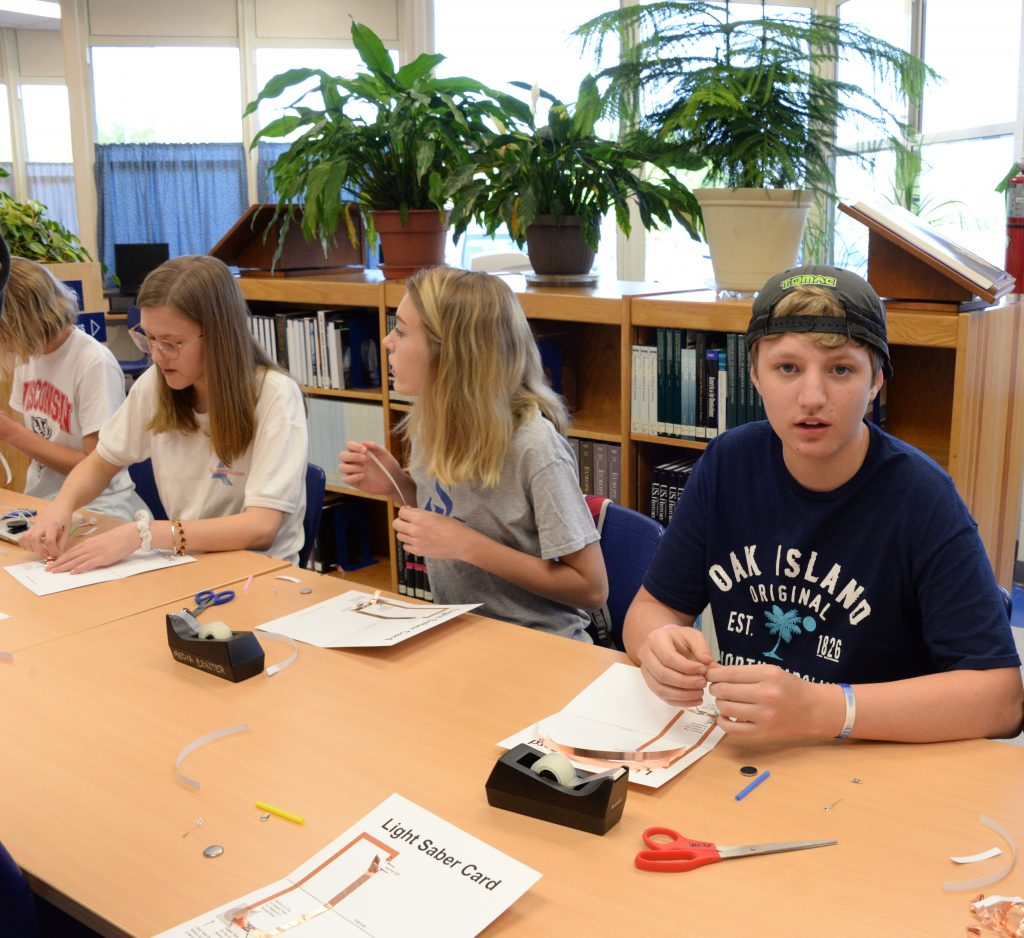 Students add copper tape to a template to create a lightsaber.